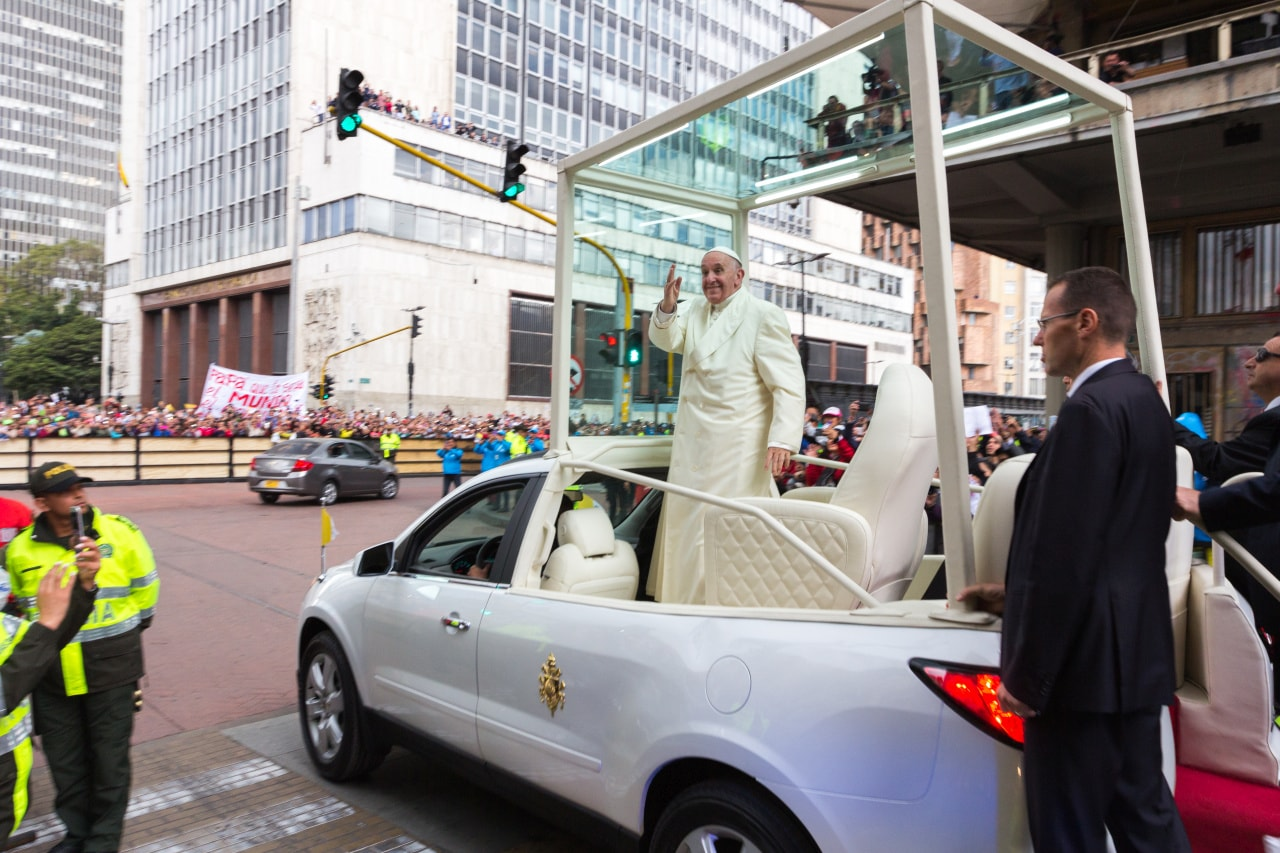 Pope Francis waves to passerbys along the 7th avenue of Bogotá's central district.