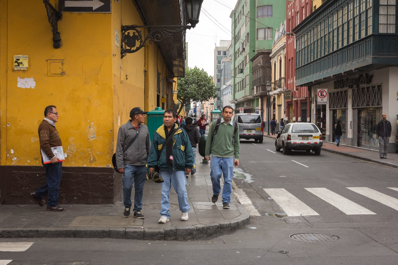 Men on a street corner in the city centre of Lima, Peru.
