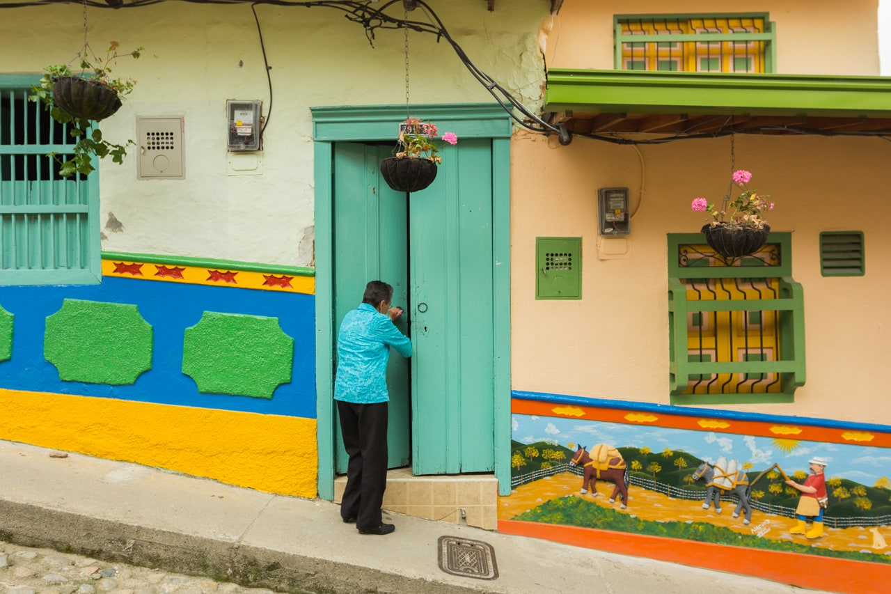 A resident of Guatapé enters her house. Many residences and buildings in the town of Guatapé have been decorated in this manner.